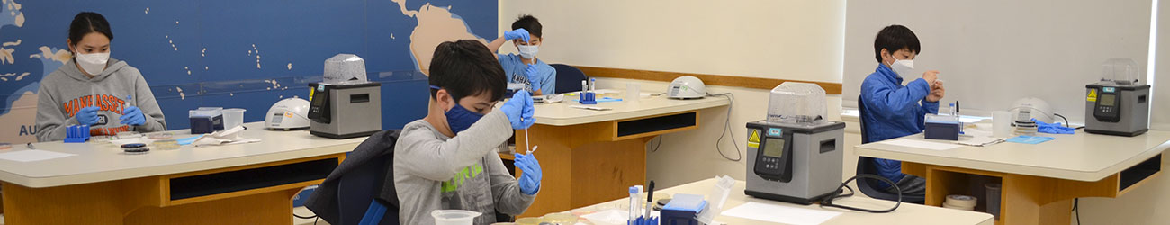 students in masks working in a laboratory
