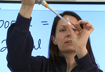 Teacher demonstrates using a micropipette